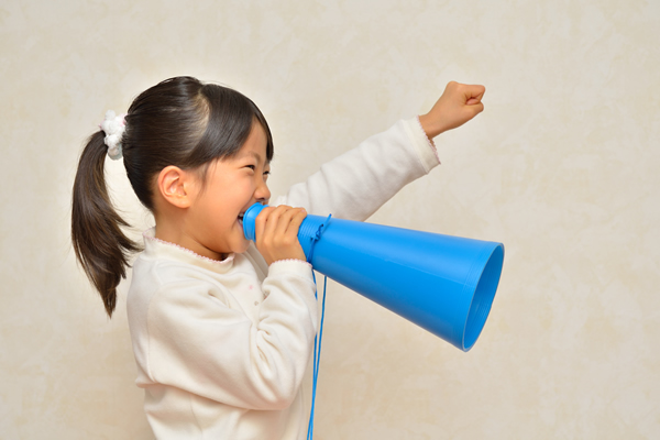 A young girl in a white sweater speaking into a blue megaphone